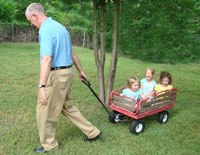 Gary pulling his granddaughters in a little red wagon